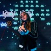 andre-hunter-ugjPgy2BQug-unsplash: A young woman posing in front of a Space Invaders background
